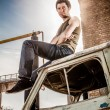 man in singlet and jeans sitting on roof of old minibus — Stock Photo