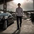 Man walking near black luxury car against industrial background — Stock Photo