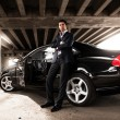 Man in suit leaning against black expensive car under bridge — Stock Photo