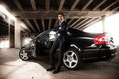 Man in suit leaning against black expensive car under bridge — Stock Photo