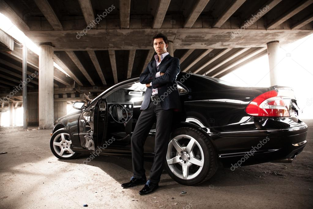 Uber Price Quote >> Man in suit leaning against black expensive car under bridge — Stock Photo © Kryzhov #36372583