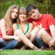 Two girls and young man sitting on meadow with crossed legs — Stockfoto #36389099