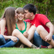Brother and sister kissing younger sister while sitting on grass — Stock Photo