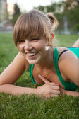 Portrait of young woman smiling while lying on grass — Stock Photo