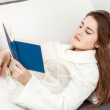 Smart woman in white sweater lying on sofa and reading book — Stock Photo