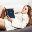 Brunette woman in sweater lying on sofa and reading book — Stock Photo #36668241
