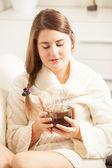 Brunette vrouw zittend op de bank over het houden van vaporing thee — Stockfoto