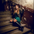 Sexy girl sitting on stairs at old grungy building — Stock Photo #36729405