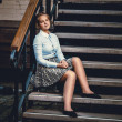 Portrait of young woman in shirt and skirt sitting on old stairs — Stock Photo