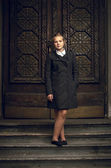 Blond girl standing old stairs in black raincoat — Stockfoto
