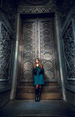 Fashionable woman leaning against high threaded gates — Stockfoto