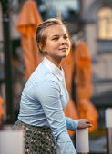 Cute young woman standing on summer terrace at restaurant — Stock Photo