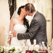 Bride and groom kissing passionately behind table at banquet — Stock Photo