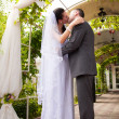 Bride and groom hugging and kissing under wedding arch — Stock Photo