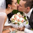 Couple kissing passionately and holding wedding bouquet — Stock Photo #36791665
