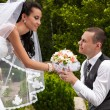 Handsome groom giving wedding bouquet to bride at park — Stock Photo