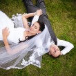 Portrait of newly married couple lying on grass and holding hands — Stock Photo #36791735