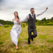 Married couple running and jumping in park while holding hands — Stock Photo