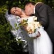 Groom kissing passionately bride in neck neck under tree — Stock Photo