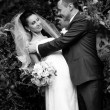 Foto de Stock  : Wedding portrait of groom hugging bride and smiling at her