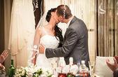Noiva eo noivo beijando apaixonadamente atrás da mesa do banquete — Foto Stock