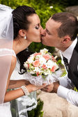 Couple kissing passionately and holding wedding bouquet — Stock Photo