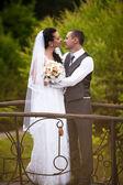 Noiva e noivo de pé na ponte e abraçando — Foto Stock