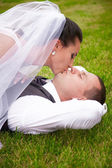 Portrait of brunette bride kissing groom lying on grass — Stock Photo