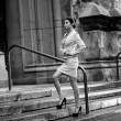 Photo of sexy businesswoman posing on stair against cathedral — Stock Photo