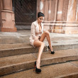 Sexy woman with long legs in classic suit sitting on old stairs — Stock Photo