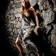 Blond woman in long dress leaning against ancient stone wall — Stock Photo #37109585