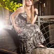 Blond woman in long dress sitting at old courtyard — Stock Photo