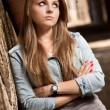 Blonde girl in jeans coat leaning against wall and looking aside — Stock Photo