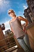 Woman in jeans and singlet wearing sunglasses on street — Stock Photo