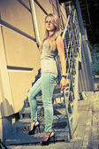 Sexy woman in jeans and heels leaning against metal railings — Stock Photo