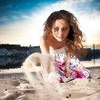 Stock Photo: Curly woman in dress sitting on beach and throwing sand