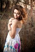 Brunette vrouw in de zomer jurk bij forest in zonnestralen — Stockfoto