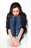 Sad brunette woman in leather coat and jeans sitting on floor — Stock Photo