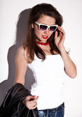 Portrait of brunette woman in white singlet and sunglasses — Stock Photo