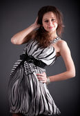 Sexy brunette with dress and hair lifted by wind at studio — Stock Photo