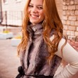 Portrait of cute redhead girl smiling on street — Stock Photo