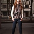 Redhead woman in fur coat and jeans standing on street — Stock Photo #37165595
