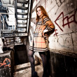 Redhead woman in coat leaning against wall under metal stairs — Stockfoto