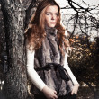 Edhead woman in fur coat leaning against old tree at park — Stock Photo #37165927