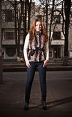 Redhead woman in fur coat and jeans standing on street — Photo