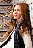 Sexy redhead sitting on stairs and leaning against brick wall — Stock Photo