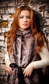 Sexy redhead girl in fur coat leaning against brick wall — Stock Photo