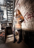 Redhead woman in coat leaning against wall under metal stairs — ストック写真