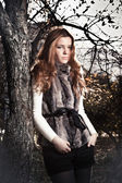 Edhead woman in fur coat leaning against old tree at park — Stock Photo