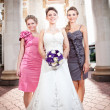 Bride with two bridesmaids against colonnade — Stock Photo